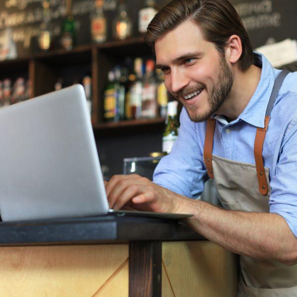 Barman aan de bar met laptop